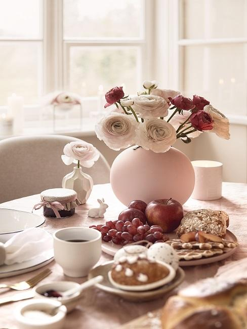 Blumenarrangement in rosa Kugelvase auf Esstisch
