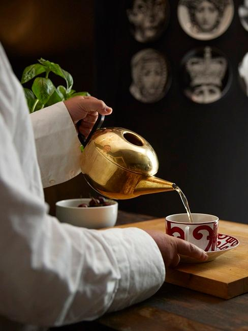 Mann schenkt Tee ein