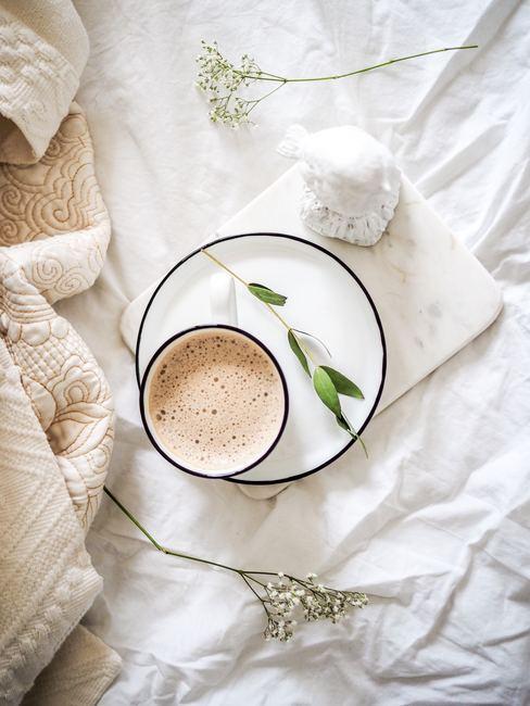Taza de te sobre cama con sábanas blancas
