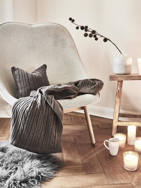 Witte stoel met houten salontafel en grijse dekens