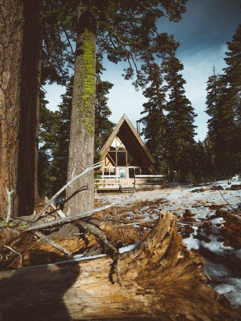Houten huis met puntdak in het bos met een kleine laag sneeuw op de grond