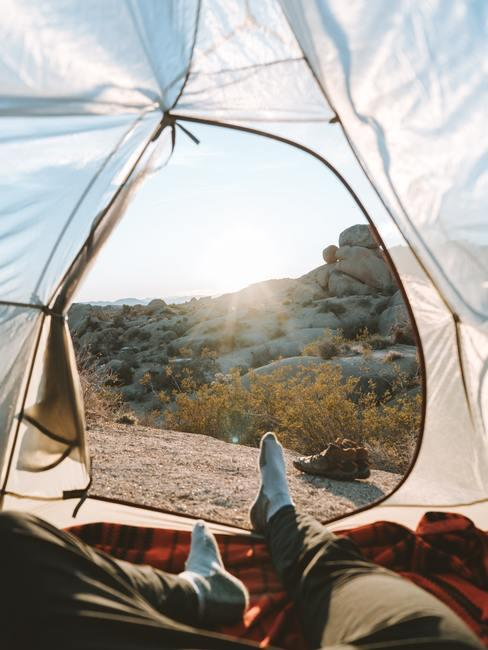 Uitzicht vanuit de tent op een berg met voeten in beeld