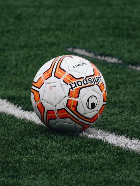 Wit met oranje voetbal op groen voetbalveld