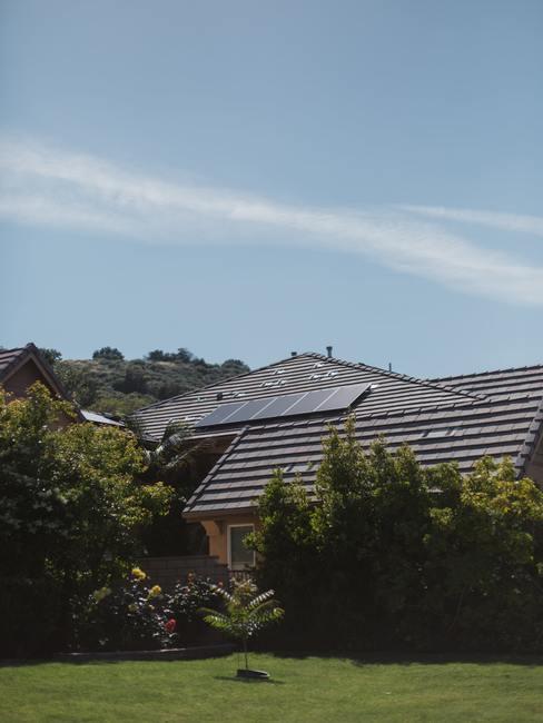 Zonnepanelen op schuin dak met groene voortuin