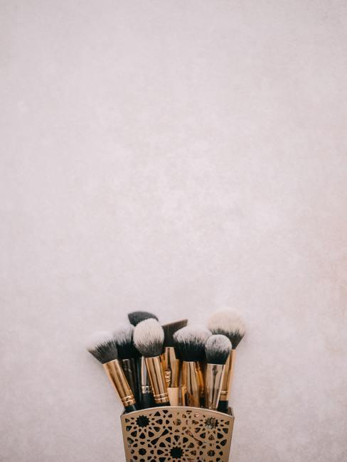 Roze achtergrond met penselen in gouden bakje