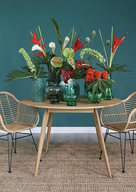 Houten tafel met groene bloemen voor groene wand in groene vazen