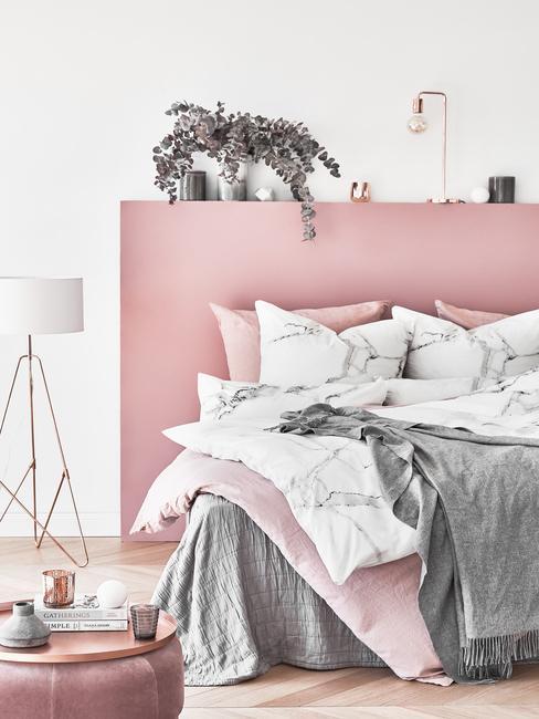 Slaapkamer in roze met bed met verschillende kussens en decoratief lamp, planten en accesoires
