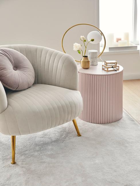 Beige stoel op zandkleurig vloerkleed met oud roze bijzettafel en gouden accessoires