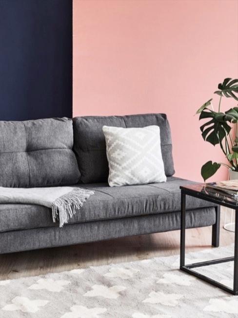 Futon Sofa in Grau mit Kissen, davor ein Teppich und ein Couchtisch mit Deko