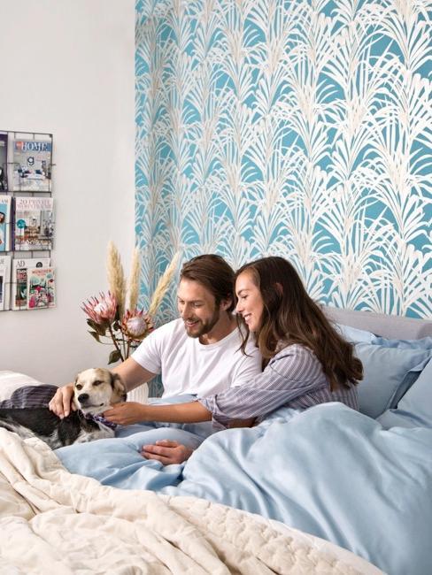 Pärchen mit Hund im Bett vor blau gemusterter Tapete