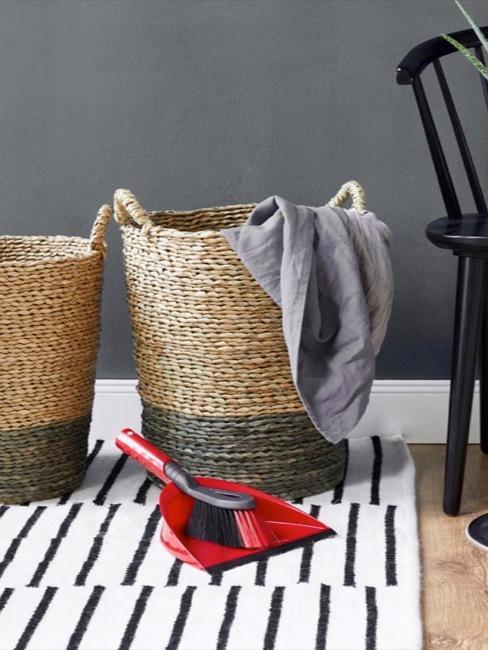 Aufräumen: Reingungsutensilien auf schwarz-weißem Teppich neben Aufbewahrungskörben und schwarzem Stuhl