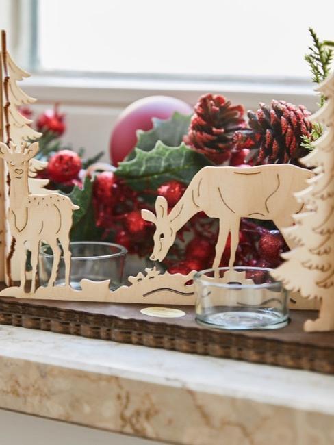 Adventsdeko mit Zweigen, roten Christbaumkugeln und Holzfiguren