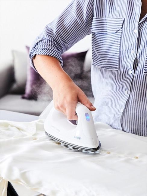 Frau die weißes Hemd bügelt