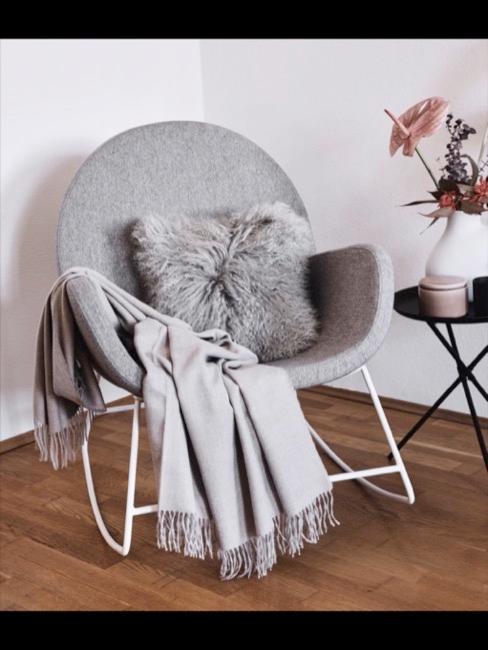 Grauer Stuhl mit grauem Fellkissen und Decke