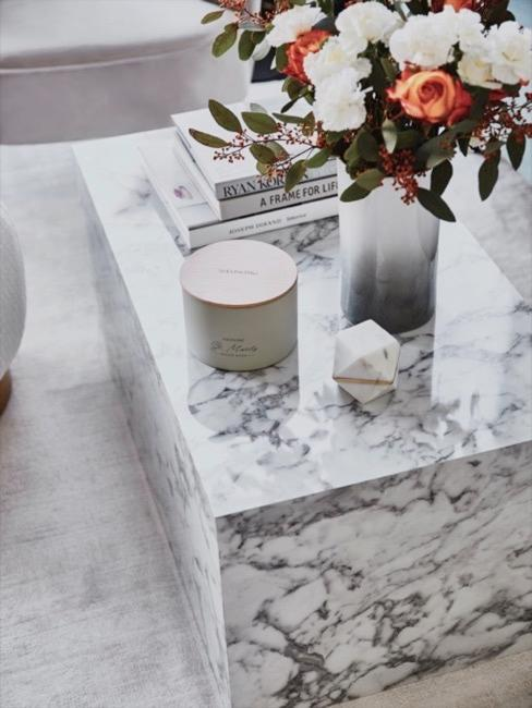 Cube en marbre blanc gris décoré avec bouquet de fleurs, livres déco et bougies.