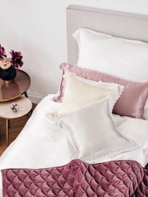Cama gris clarito con cojines y mantas en rosa y blanco y terciopelo y seda