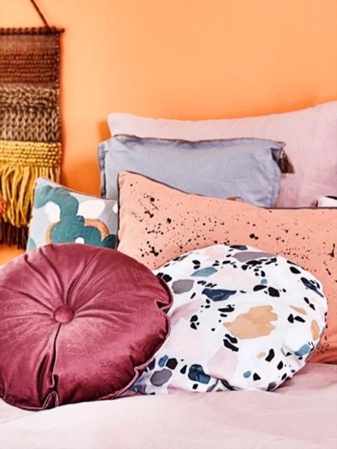 Kissen im hellen Terrazzo Look auf Bett vor orangener Wand