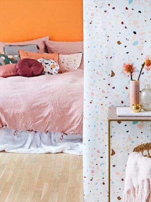 Schlafzimmer mit Bett in rosa, orange und Terrazzo Wand mit Konsolentisch im Vordergrund