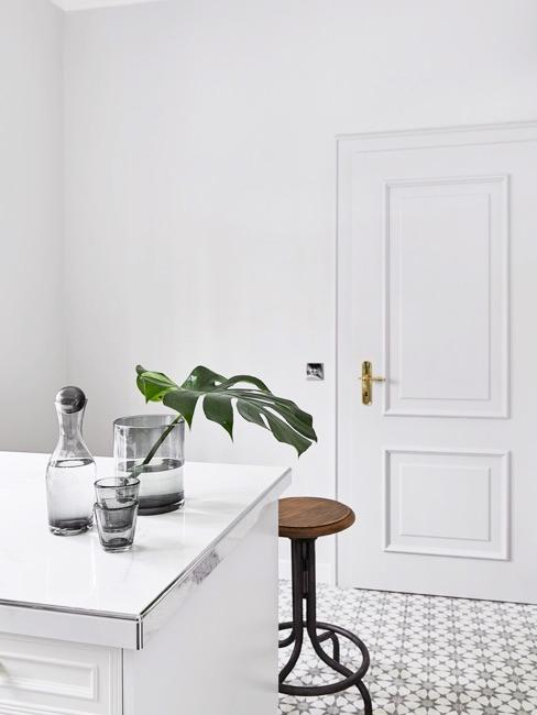 Nahaufnahme Küche in weiß mit Deko und Holzhocker