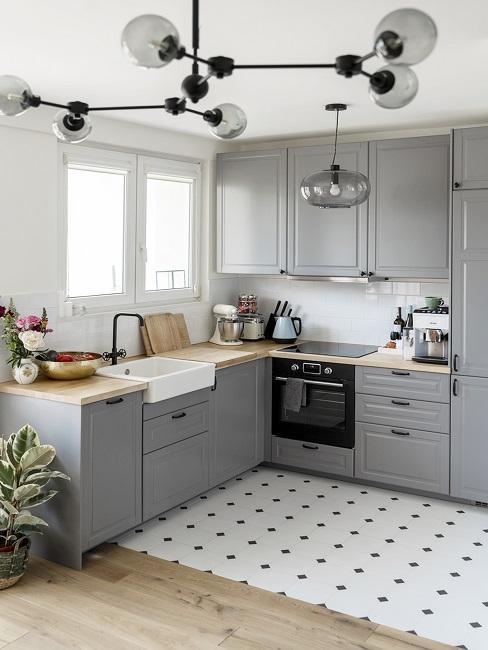 Graue Küche mit weißen Fliesen und Arbeitsfläche aus hellem Holz