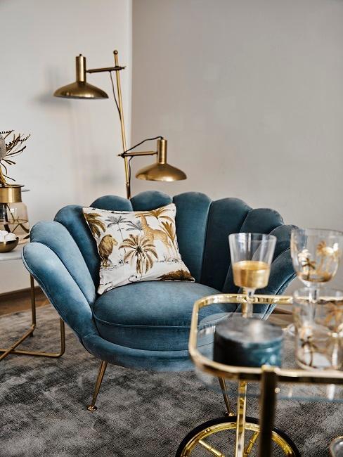 Poltroncina vintage in velluto blu vicino a tavolino da caffè