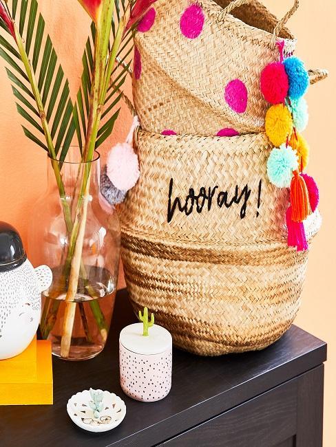Pflanzenkörbe mit bunten Bommeln neben einer Vase und Hippie Deko