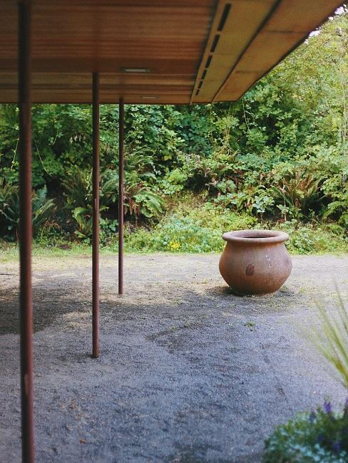Pergola Pavillon im Garten, daneben ein großer Tontopf