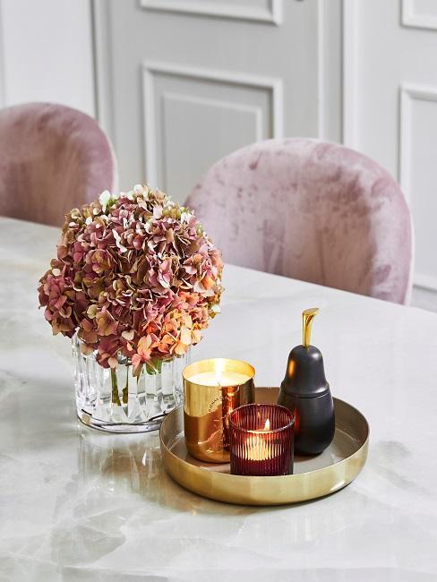 Goldene Dekoschale mit einer Duftkerze und einem Windlicht auf einem weißen Marmor-Tisch mit Hortensien in hellem Rosa in einer transparenten Glasvase