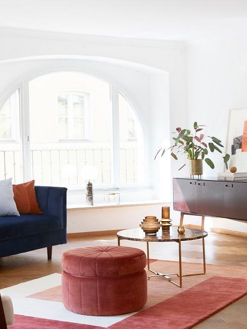 Wohnzimmer mit einem Sofa, Pouf und einem Teppich in Herbstfarben eingerichtet