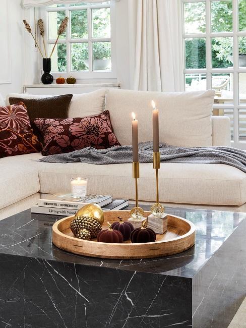 Ein schwarzer Couchtisch steht im Wohnzimmer und trägt ein Tablett mit bunter Kürbis Deko und zwei Kerzen, die brennen.
