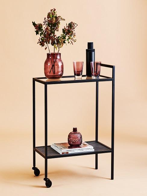 Rollwagen mit einer bunten Vase und Zweigen darin
