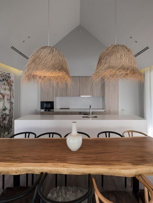 Großer Holztisch vor einer minimalistischen, offenen Küche, über dem Tisch zwei Stroh-Leuchten und darauf eine Simple weiße Vase als Deko