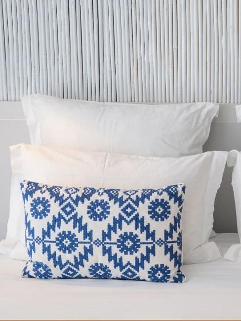 Weißes Bett mit weißen Bambusstreben im Hintergrund, auf dem Bett ein in Blau-Weiß gemustertes Deko-Kissen