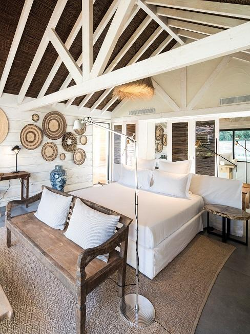 Hotelzimmer in Comporta mit einem Mix aus Weiß und Naturmaterialien beim Interior - Eine Lampe und Wanddeko aus Stroh und eine Holzbank vor dem Bett dienen als Eyecatcher