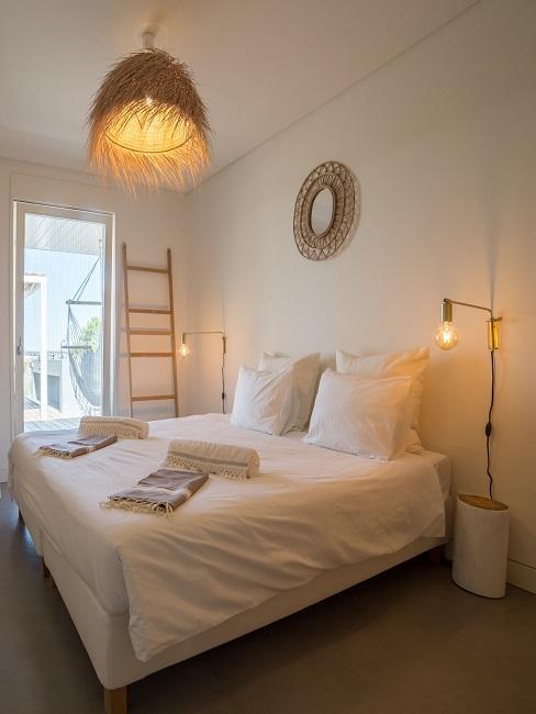 Schlafzimmer in einem Hotel, das Bett ist komplett weiß und wird durch die Strohlampe, eine Holzleiter und einen Spiegel aus Naturmaterial ergänzt