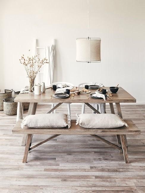 Esszimmer skandinavisch mit Holzbank und -tisch, crmefarbenen Kissen, Tischdeko auf hellem Parkett