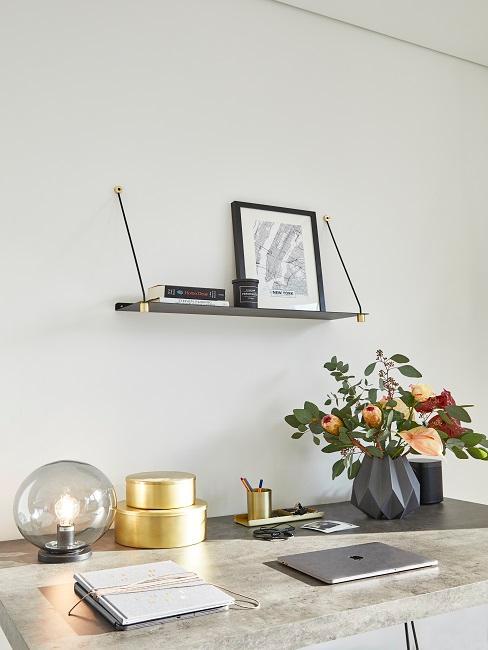 Schreibtisch mit Blumenvase, Tischleuchte, Laptop und Notizblock