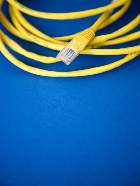 Gelbes gerolltes Kabel auf einem blauen Untergrund