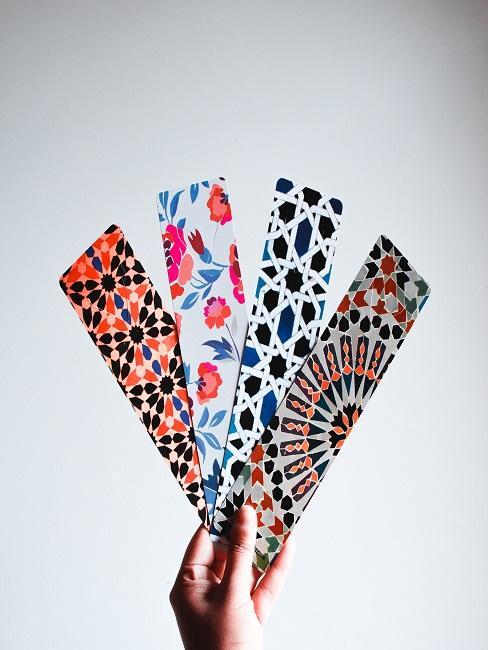 Eine Frauenhand hält vier verschiedene, bunt gemusterte Lesezeichen nach oben