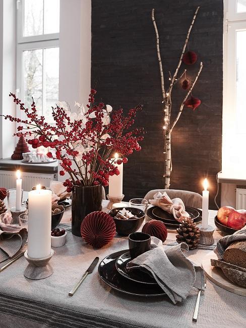 Ast dekorieren Weihnachten mit Lichtrekette hinter Tisch mit Weihnachtsdeko