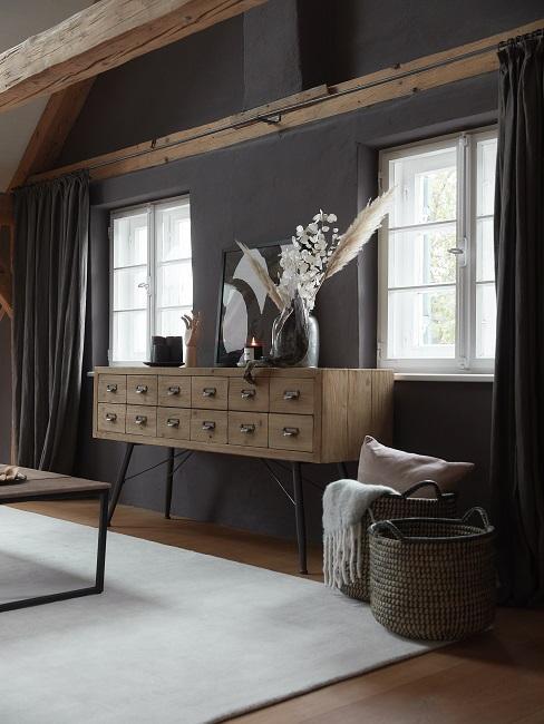Ein Holz-Sideboard im Apotheker Stil mit Deko vor einer schwarzen Wand