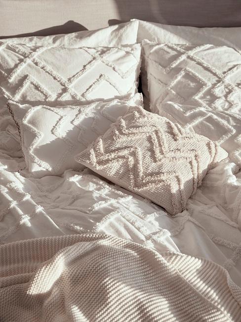 Ein Bett mit heller Bettwäsche mit Ton in Ton Zickzack-Muster und eiem Strick-Plaid