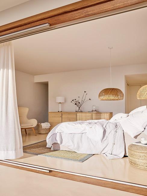 EIn helles Schlafzimmer mit Rattan-Lampen, heller Bettwäsche und einem Jute Teppich sowie einem Holz-Sideboard