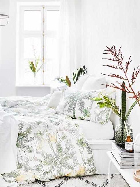 Richtig lüften Schlafzimmer mit weißen Wänden, weiß-grüner Bettwäsche und Pflanzen