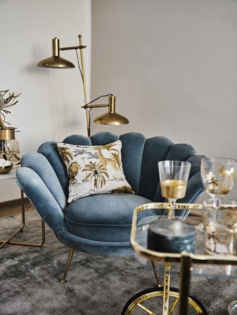 Zimmerecke mit einem goldenen Servierwagen, einem XL-Luxus-Samtsessel in Blau und Accessoires in Gold