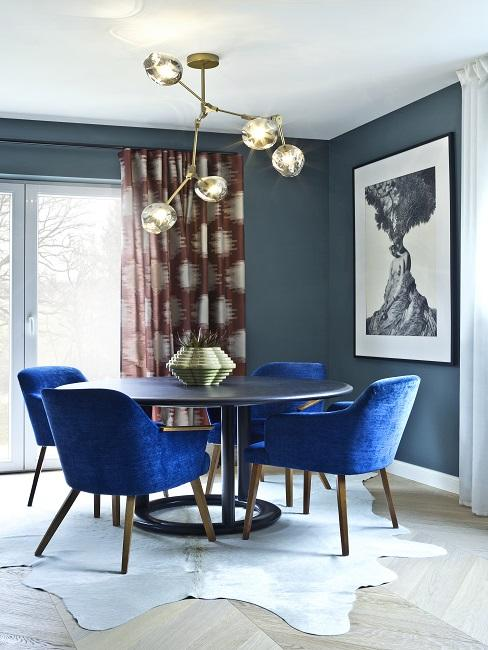 Zimmer mit Wänden in Petrol, einem runden Tisch mit Luxus-Samtstühlen in Royalblau auf einem Fell-Teppich