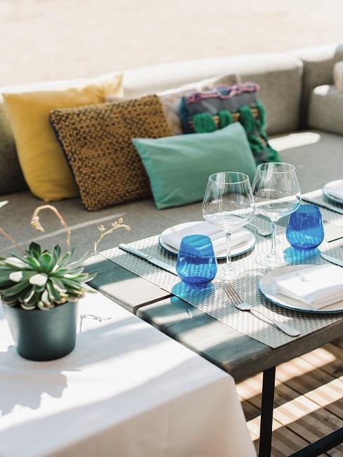 Gedeckter Tisch in einem Beachclub, die Bank ist mit bunten Ibiza Style Dekokissen dekoriert