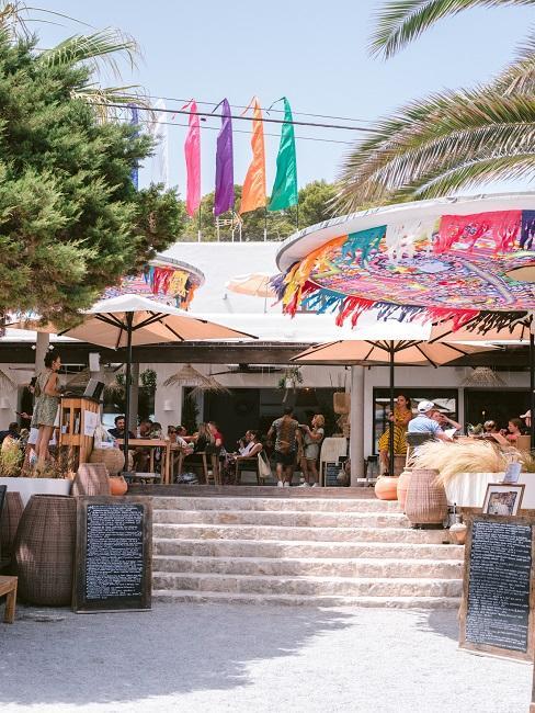 Der Eingang vom Aiyanna Ibiza mit Treppenaufgang und bielen bunten Schirmen auf und vor der großen Terrasse