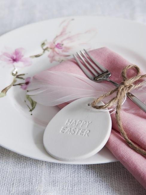 Teller mit Blumen, einer Stoffserviette und einem Osterei mit Ostergruß