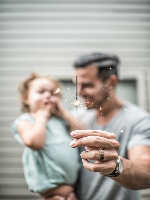 Vater mit Kind und Wunderkerze in der Hand